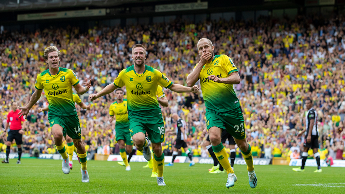 Teemu Pukki celebrates his first of three goals against Newcastle with teammates Marco Stieperman (left) and  Todd Cantwell (far left)