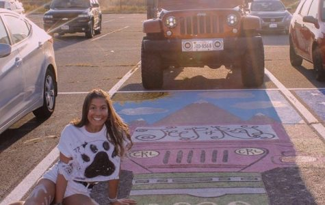Senior Cassie Rozman paints her parking spot after her jeep.